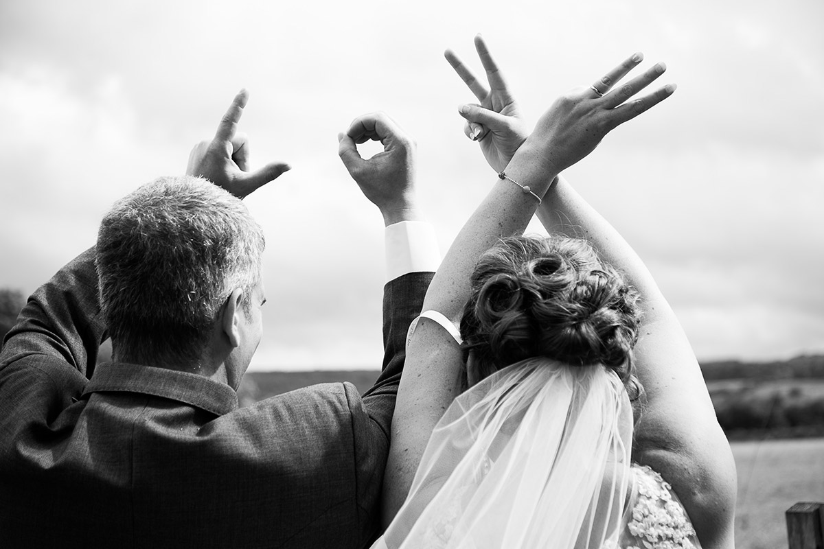Bride and groom spelling out Love with their hands. gloucestershire wedding photographer