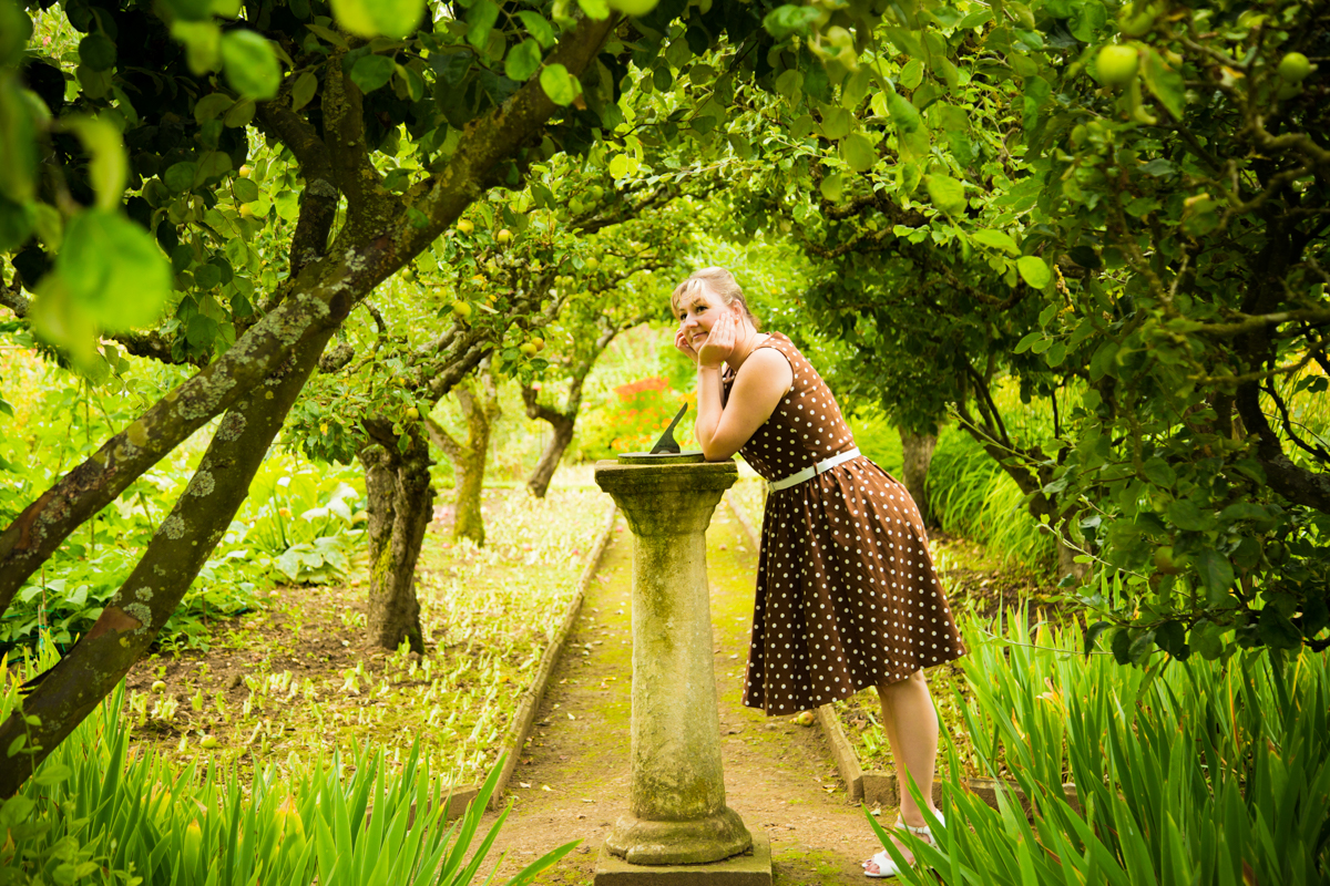 Woman stood in a country garden in Kemerton, leaning on a sun dial