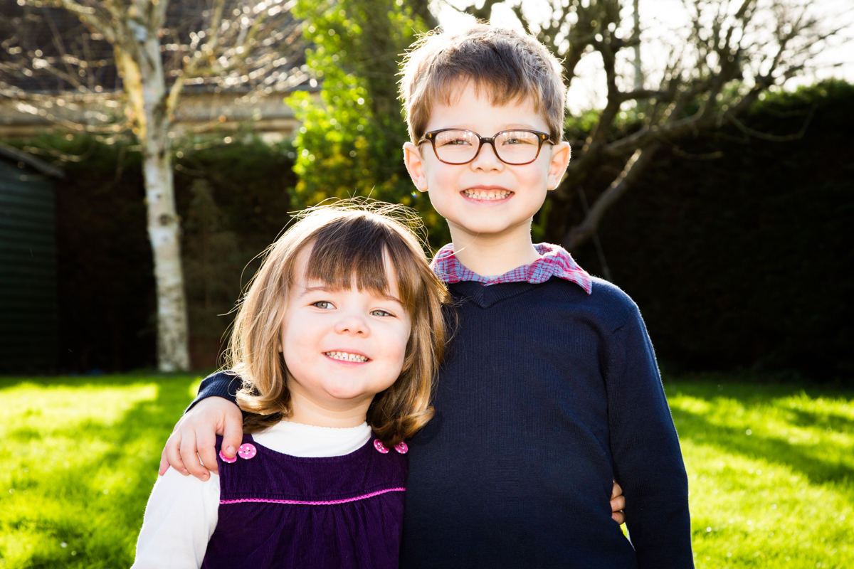 Young brother smiling, with an arm around his little sister, in a cottage garden