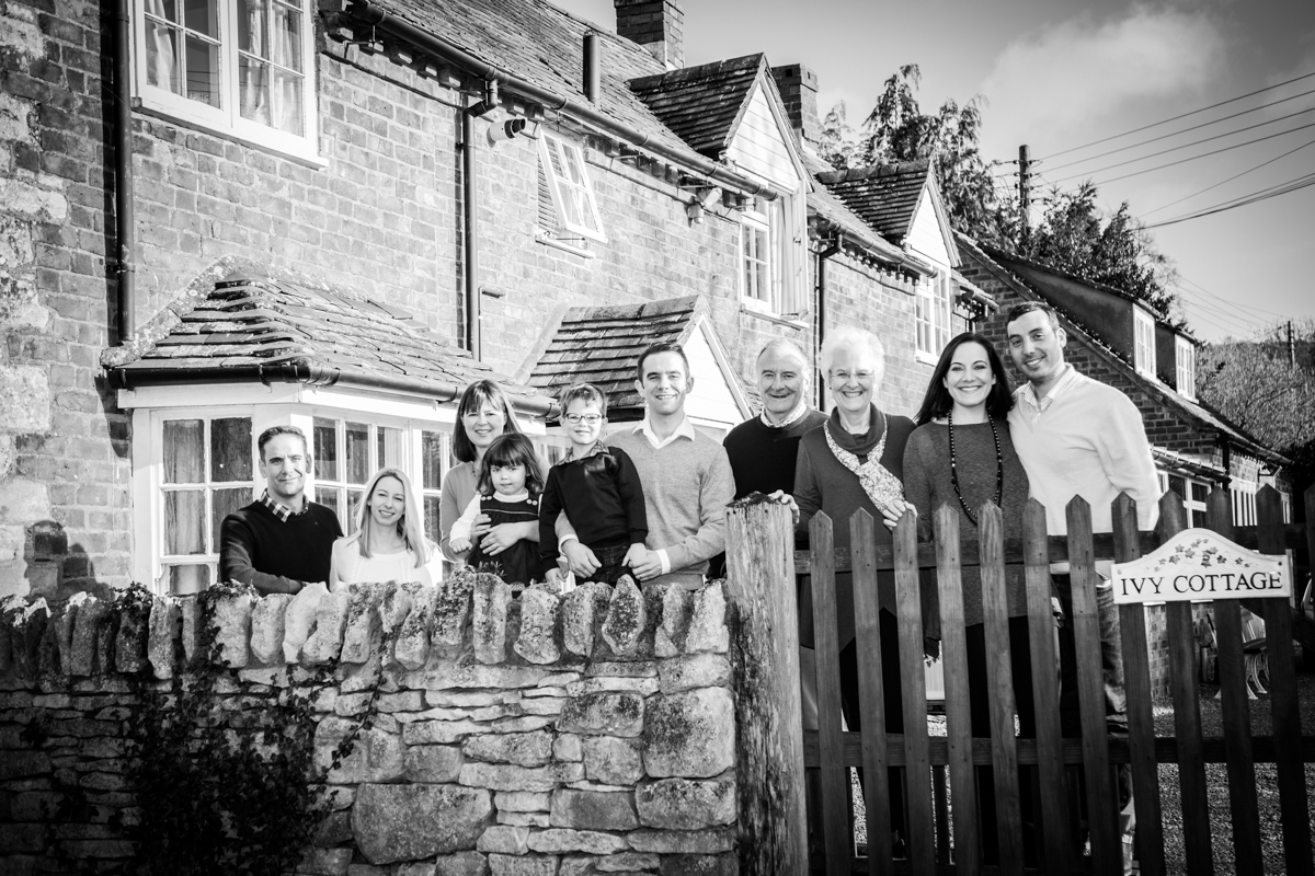 Family all standing behind a wall in a cottage garden in Bredon's Norton.