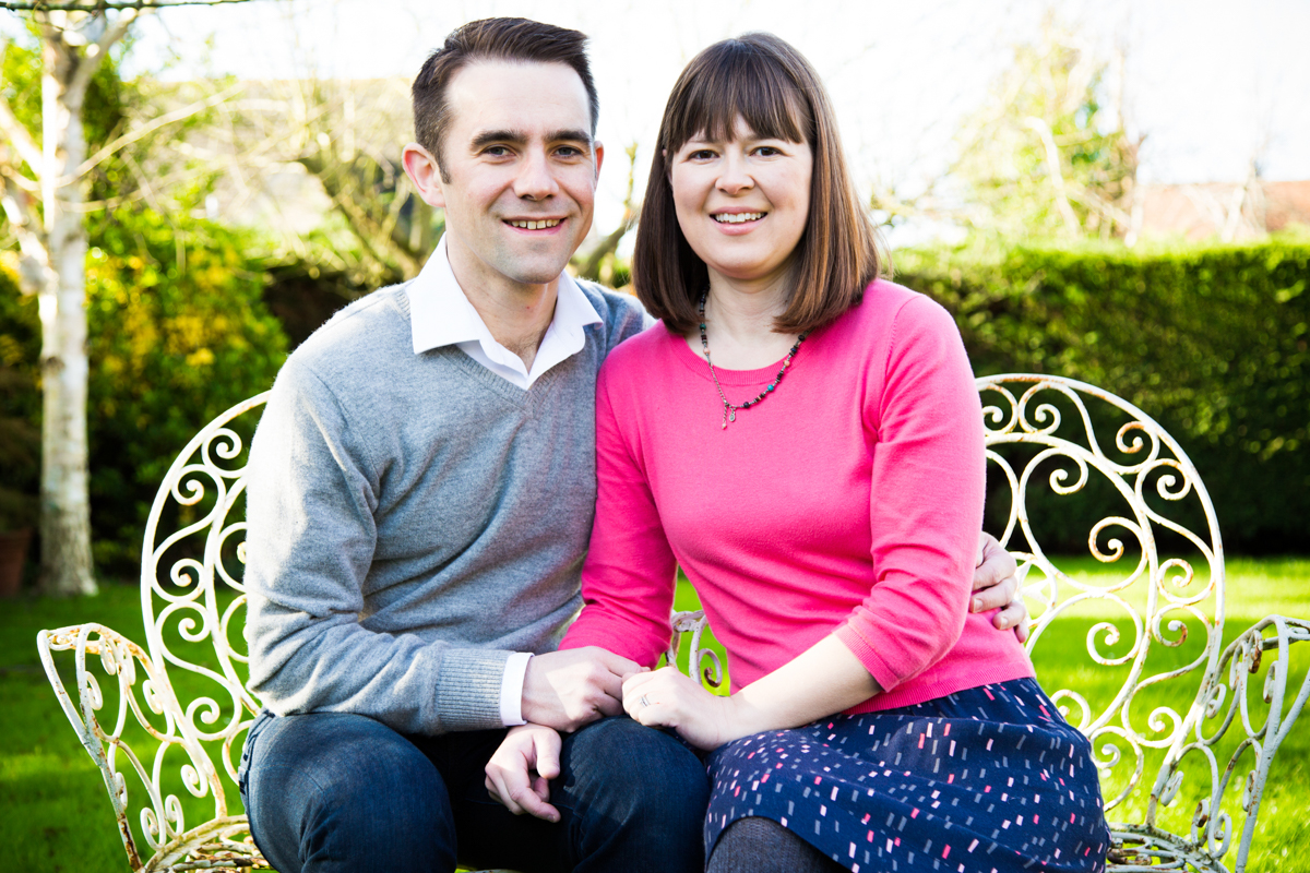 Married couple sat together on painted iron seats, in a cottage garden.