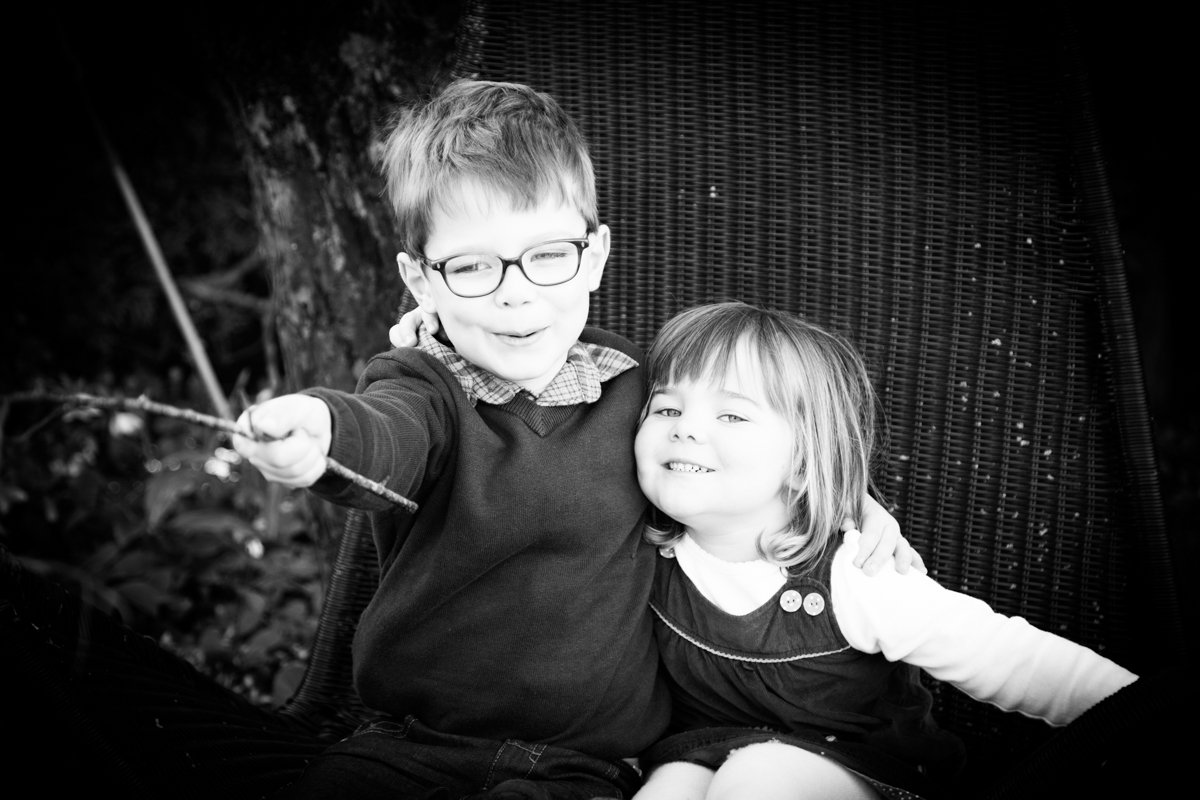 Brother and sister sat playing with a stick in a cottage garden.