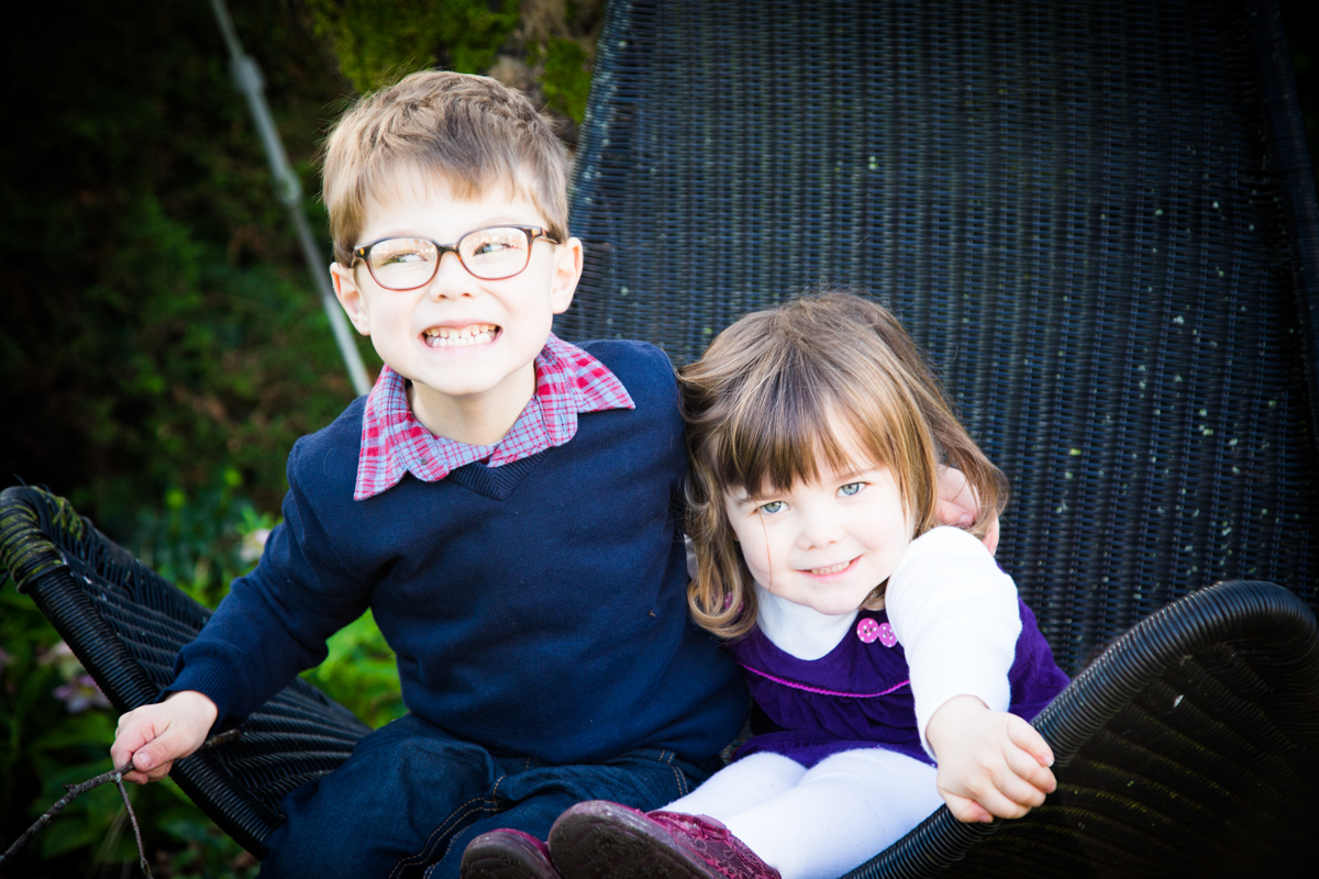 Brother and sister sat on a swinging chair in a cottage garden.