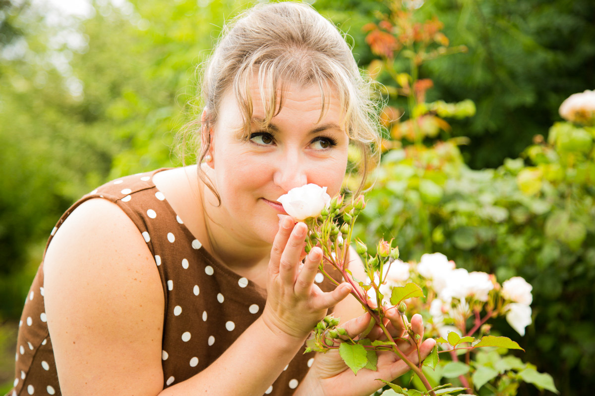Woman in a spotty dress, smelling a rose during cotswold photo shoot