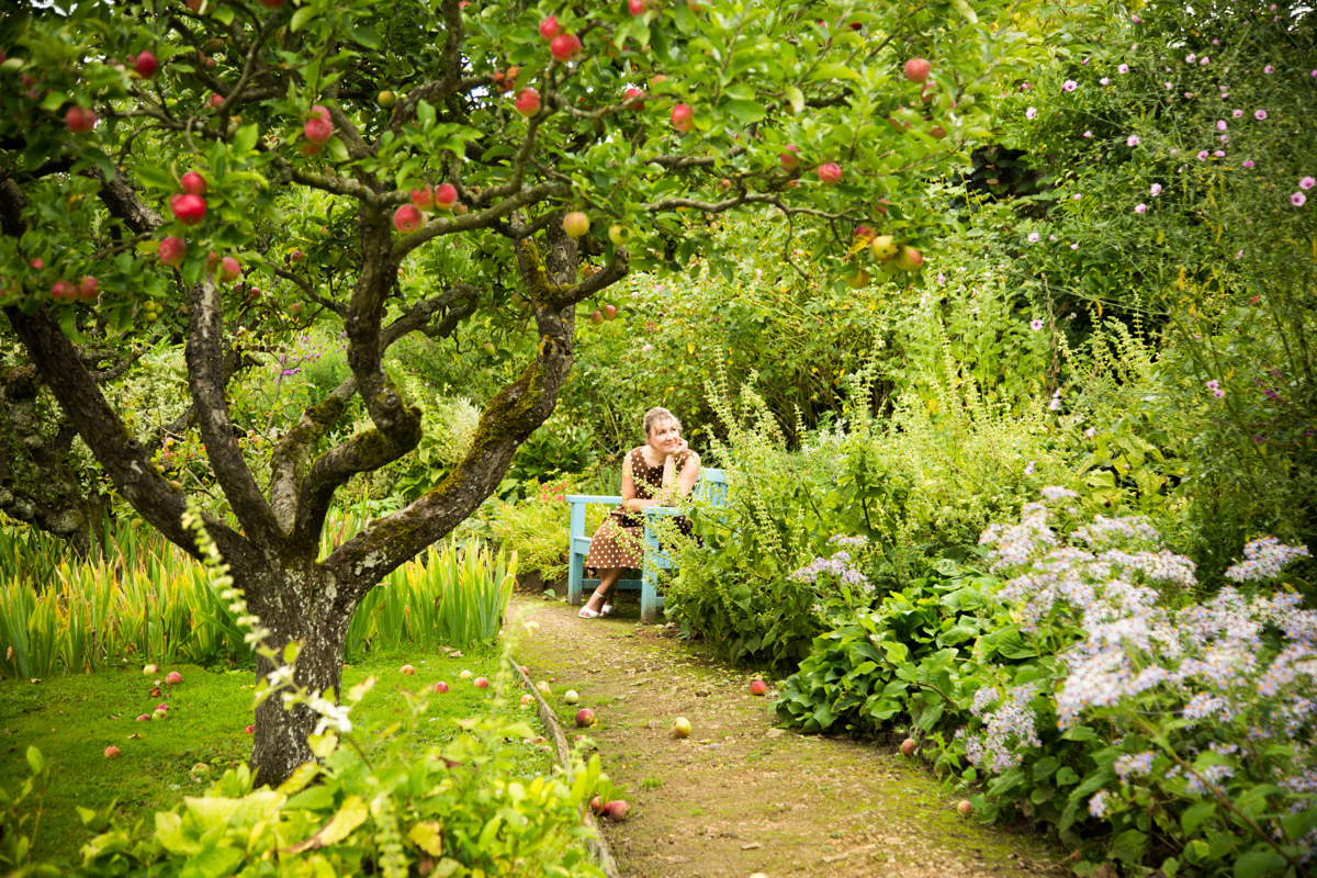 Woman sat on a bench in a cottage garden, behind an apple tree. In Kemerton, Gloucestershire.