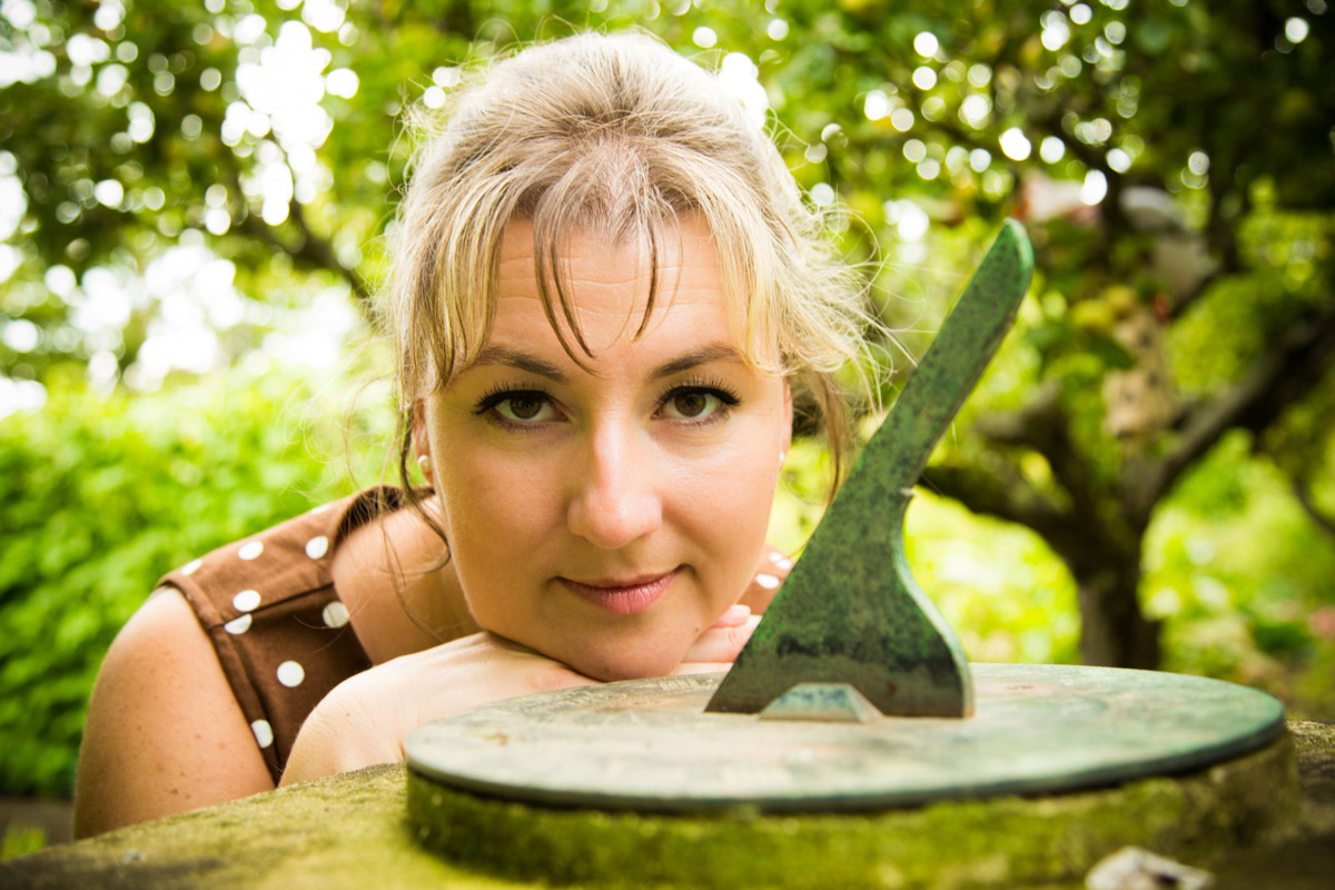 A woman with her face next to a sun dial, surrounded by greenery.