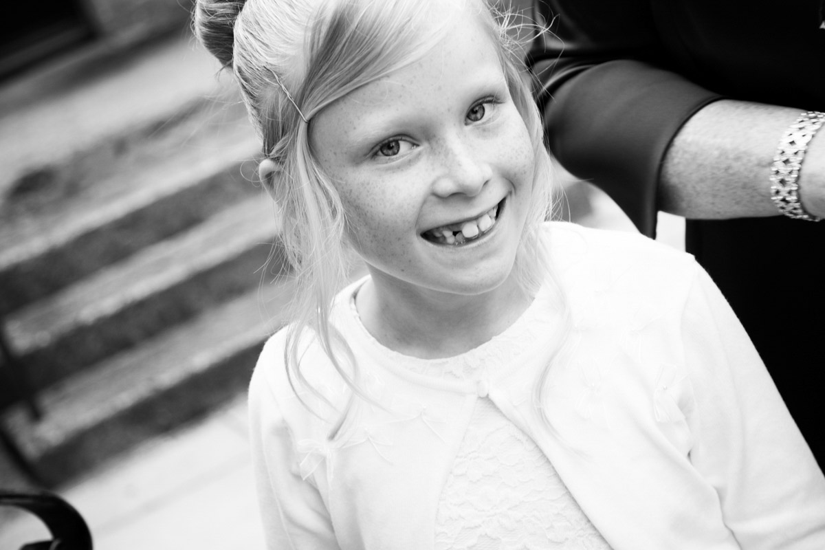 Flower girl smiling outside St Mark's Church in Cheltenham.