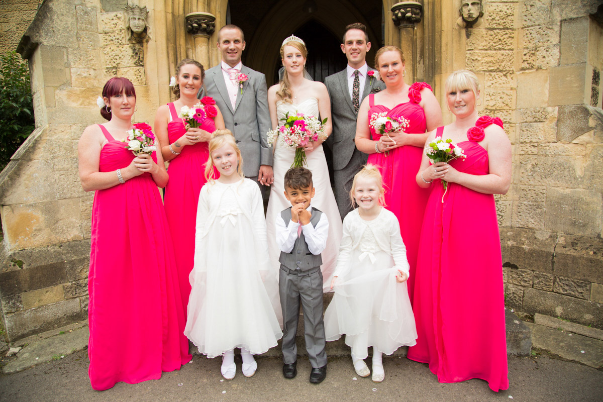 Bride and groom stood outside St Mark's Church in Cheltenham bridesmaids and best man.