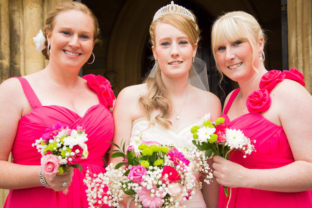 bride stood in the middle of two bridesmaids, all holding bouquets and smiling at St Mark's Cheltenham wedding