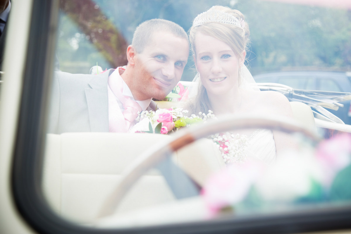Bride and groom sat in the back of the wedding car.
