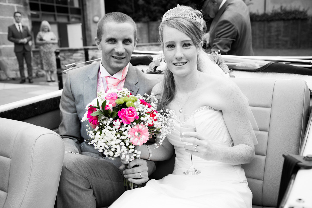 Bride and groom sat in the back of their open top wedding car.