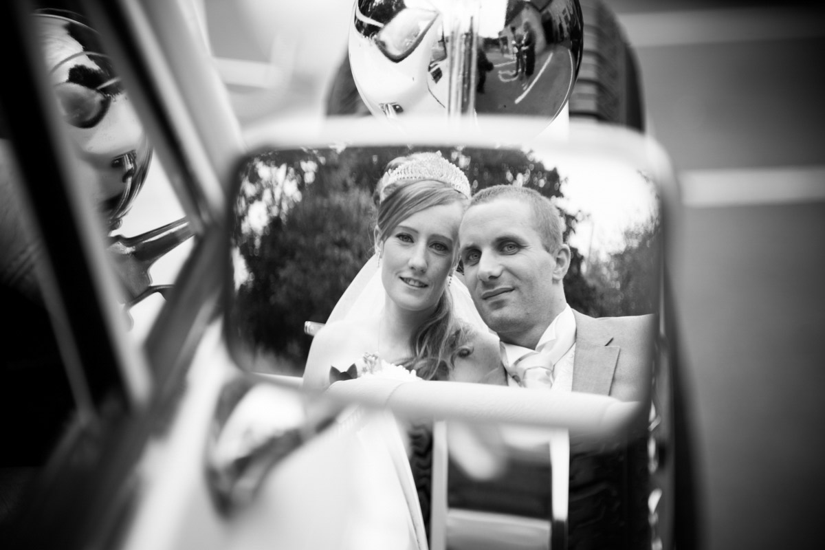 A wing mirror reflection of the bride and groom at their Cheltenham wedding.