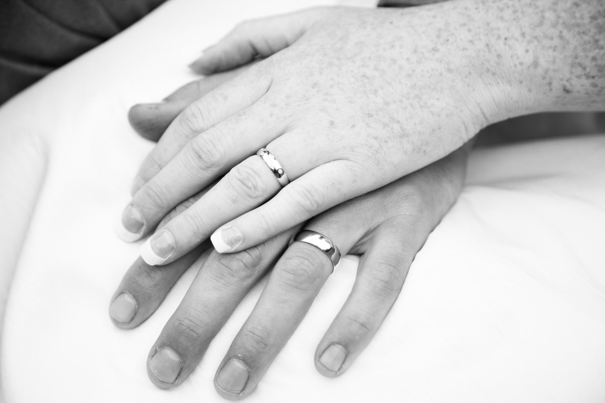 The bride and groom laying their ring hand on top of each other.