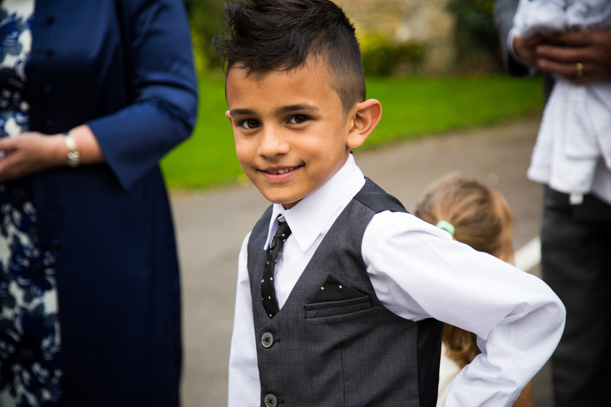 A little boy wearing a grey suit at a wedding.