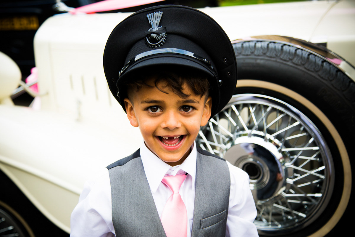 A little boy in a suit wearing the wedding car drivers hat