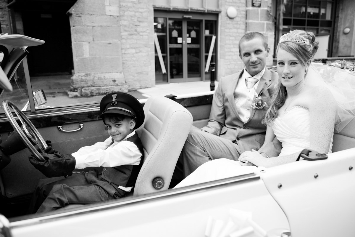 Little boy pretending to drive the wedding car