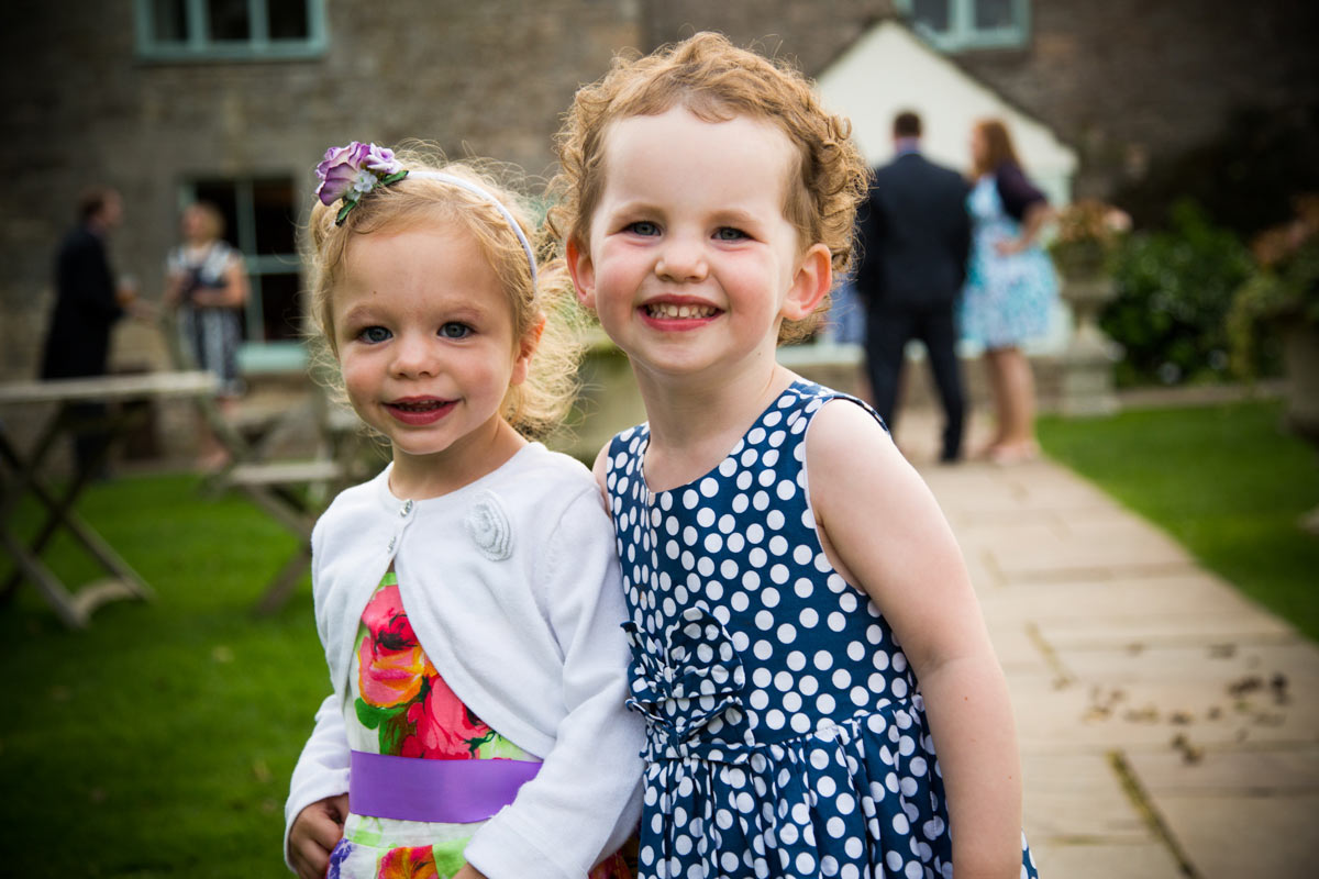 Two little girls smiling in the Old Lodge garden on Minchinhampton common.