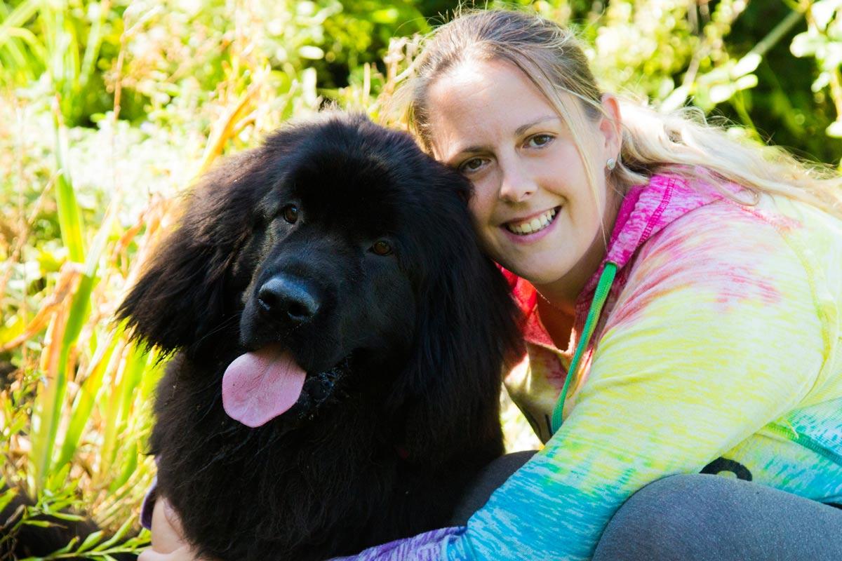 Woman cuddling her Newfoundland puppy. Worcestershire pet portrait.