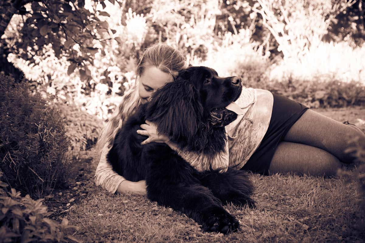 Woman lay on the grass cuddling her Newfoundland puppy.