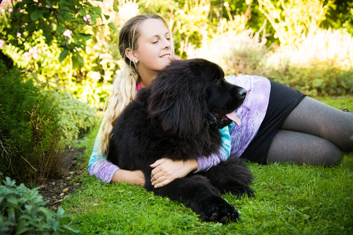 Woman lay on the grass, cuddling her Newfoundland puppy.