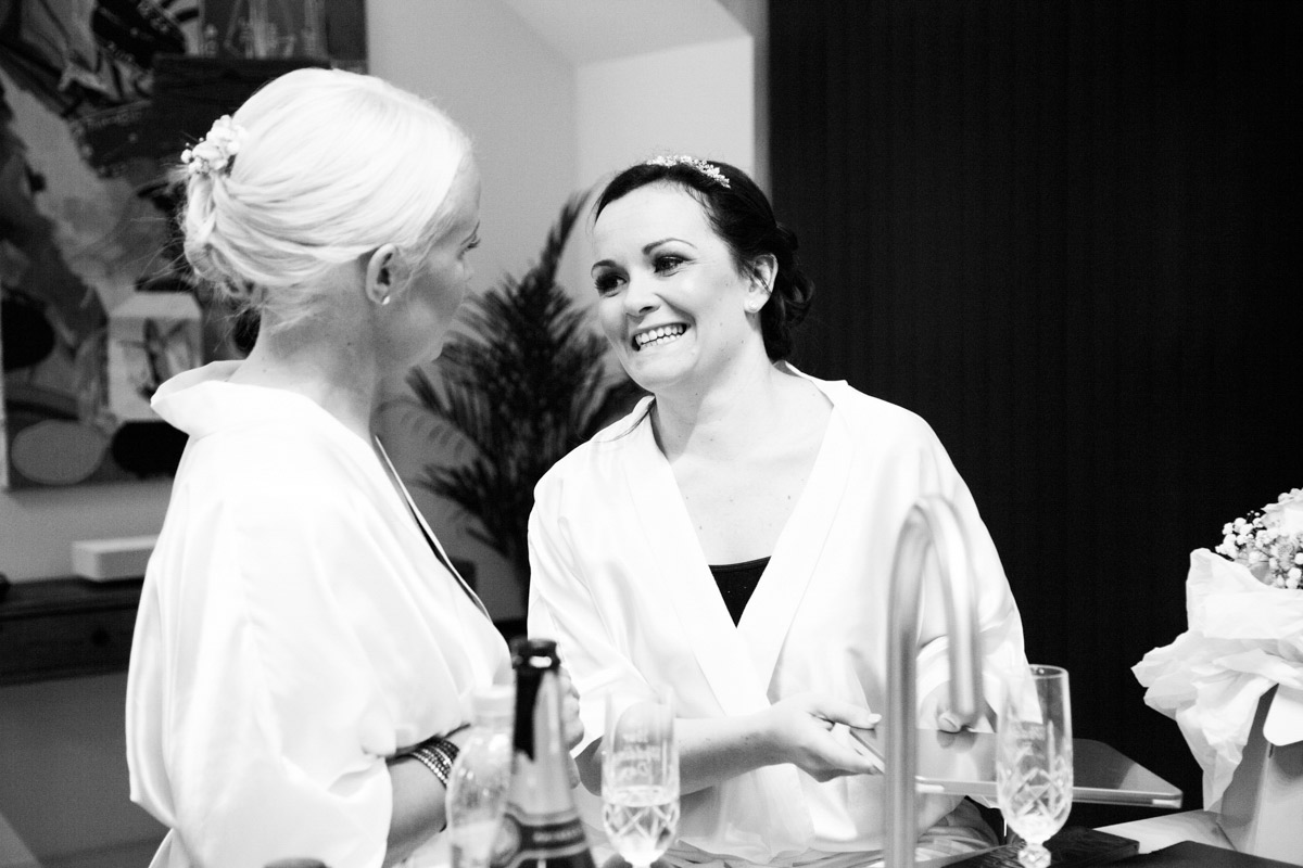 Bride happily getting ready for her wedding with her bridesmaid.
