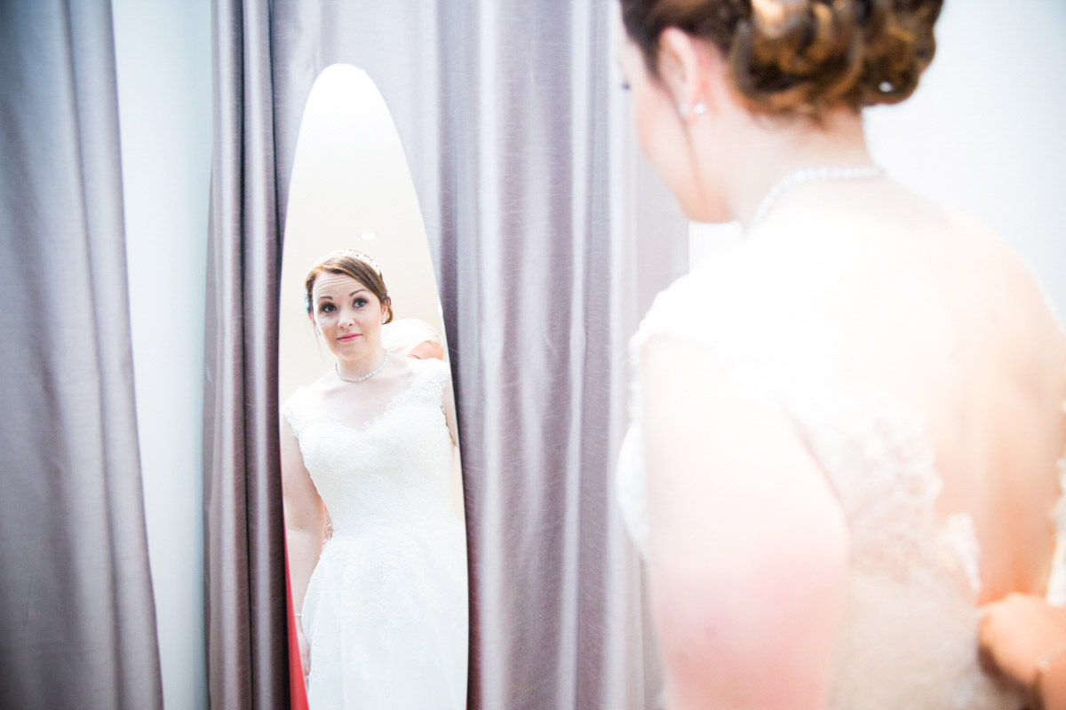 The reflection of the bride stood in her wedding dress.