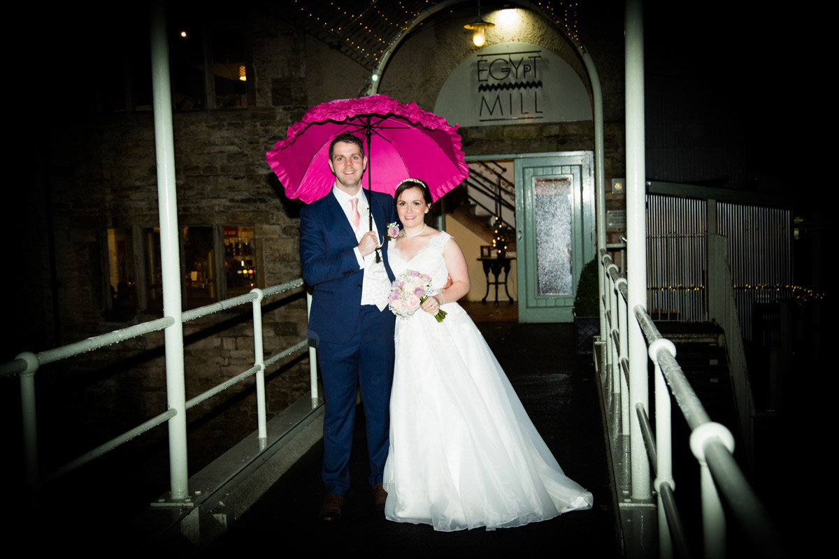 Bride and groom stood on a bride under a pink umbrella at the Egypt Mill.