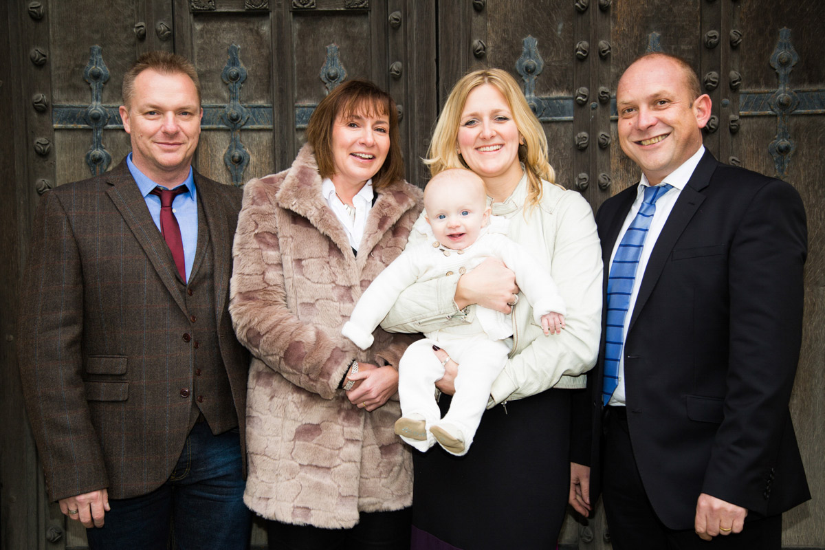 Godparents and parents holding baby boy outside Tewkesbury Abbey doors.