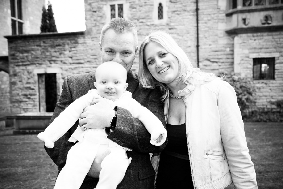 Parents holding their baby boy in the Tewkesbury abbey gardens