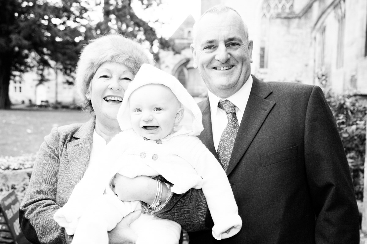 A man and woman holding a little boy at his christening