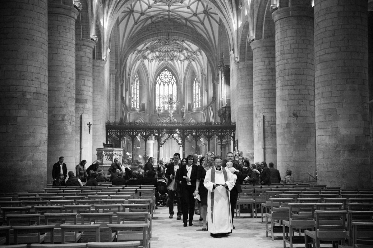 Christening guests walking inside the Tewkesbury Abbey.