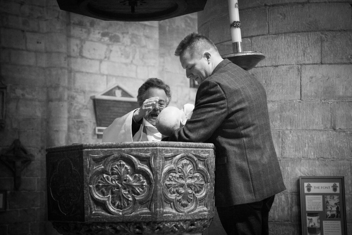Father holding baby boy whilst he is being christened in the Tewkesbury Abbey