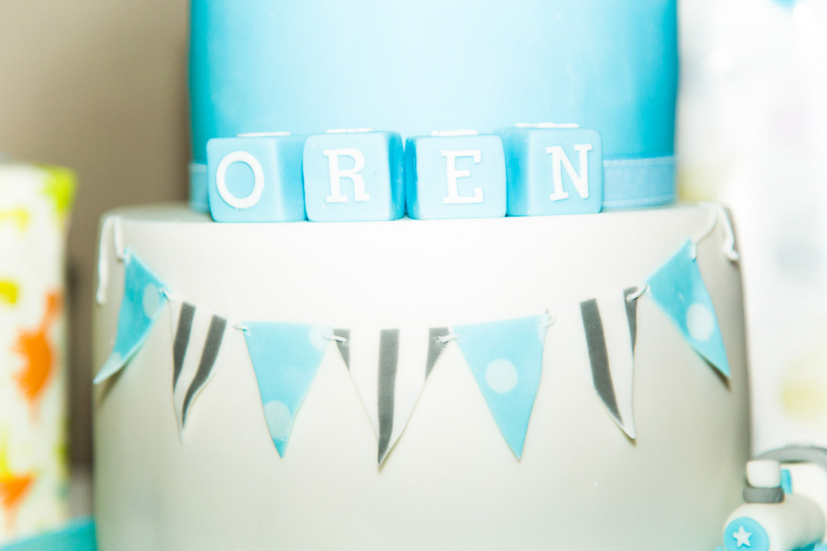 Blue and white christening cake, with building block letters and bunting.