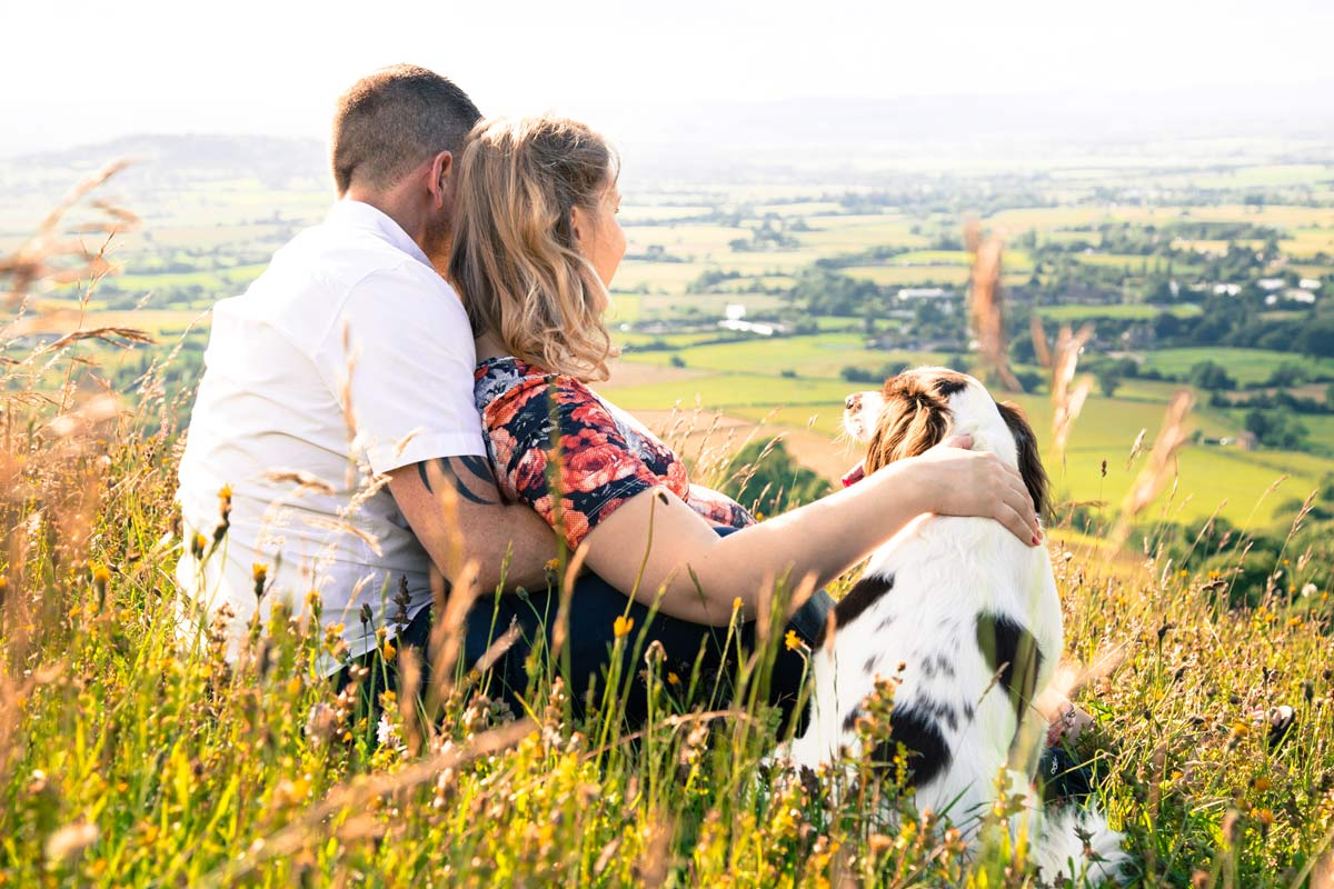 Pregnant couple sat on a hill with their dog.