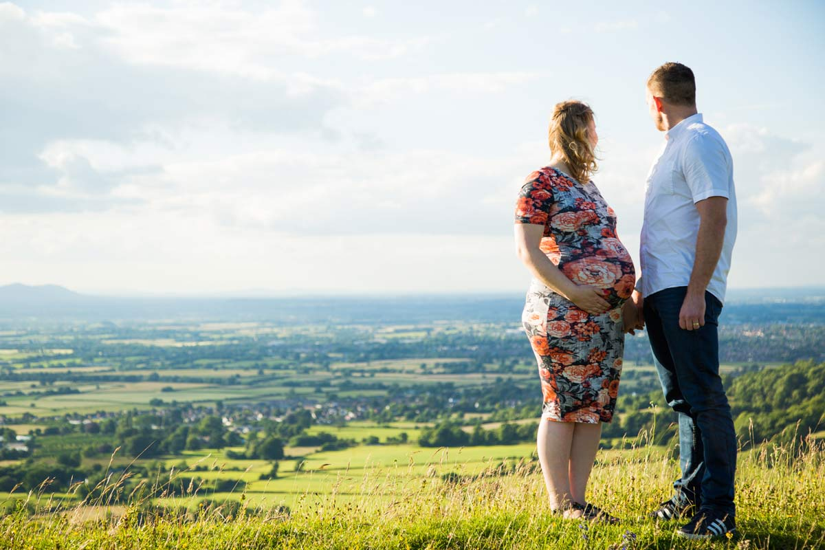 A pregnant couple stood on a hill.