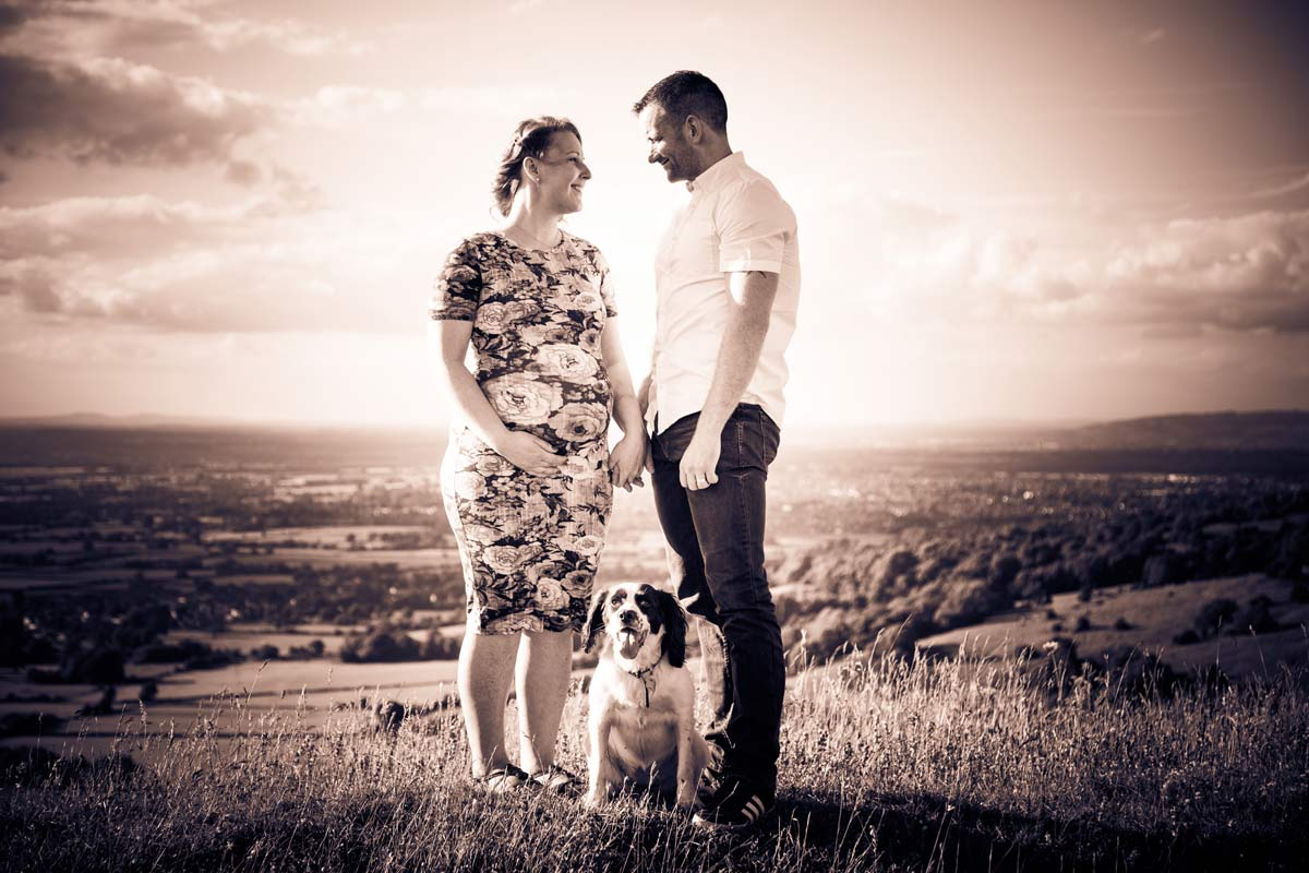 A pregnant couple stood on a hill with their dog.