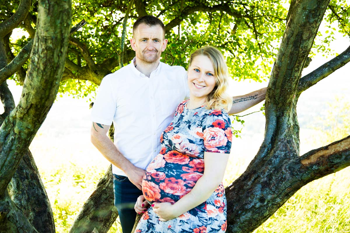 A pregnant couple leaning on a tree.