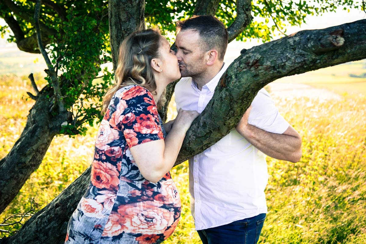A pregnant couple kissing over a tree branch.