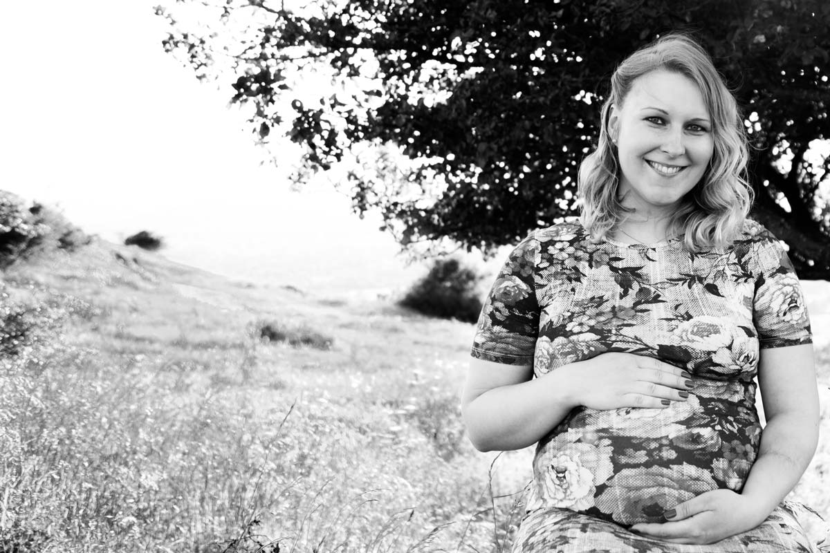 A pregnant woman sat on a hill in a floral dress.