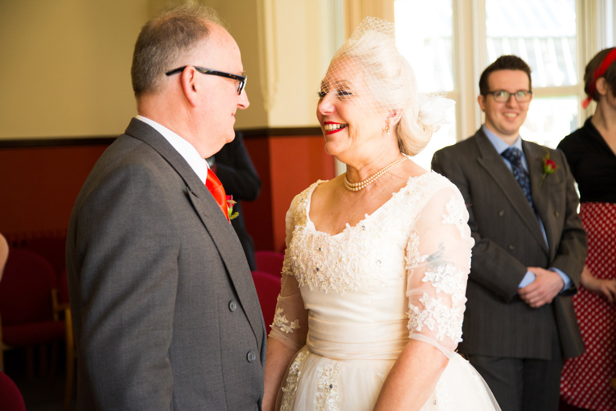 Bride and groom smiling during wedding at Glasgow registry office.