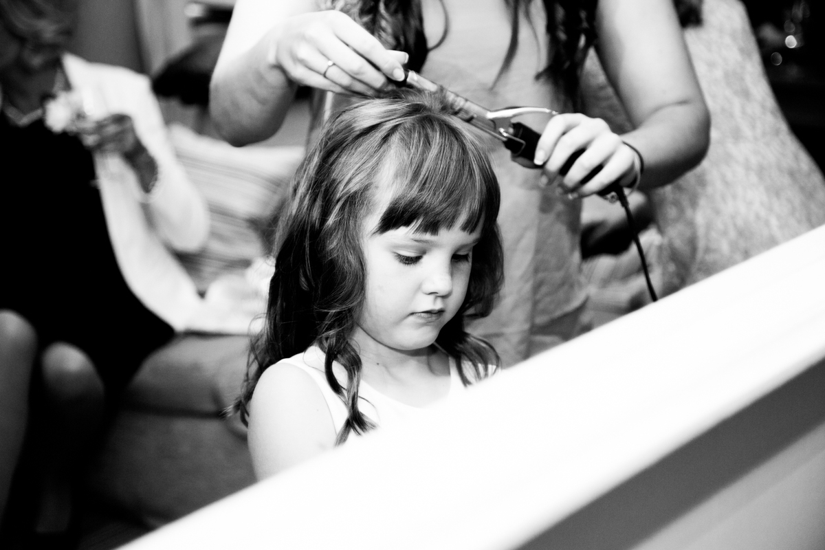 Mirror reflection of a flower girl having her hair curled at the Feathers Hotel in Ledbury.