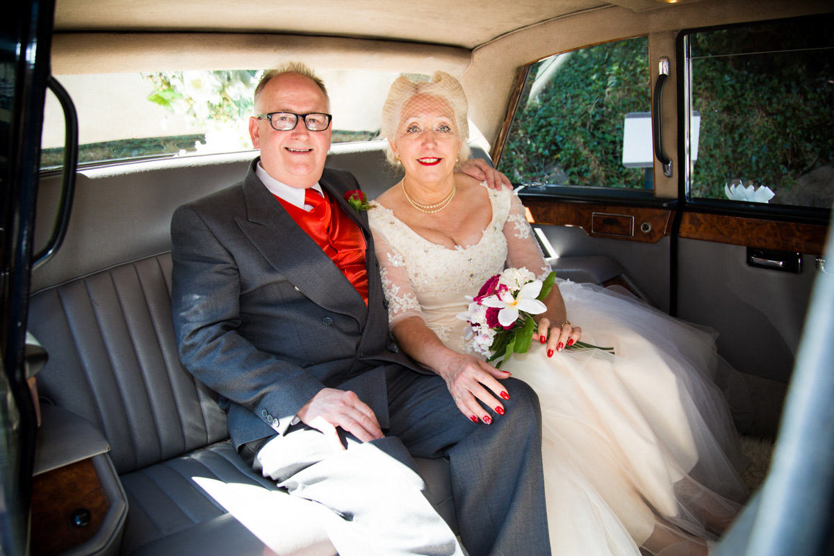bride and groom sat in the back of a wedding car outside the Glasgow Registry Office