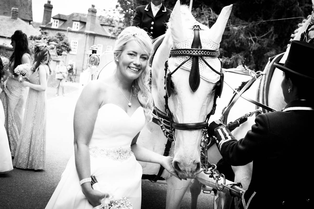 Bride stood outside St Michael's Church in Ledbury with a white horse.