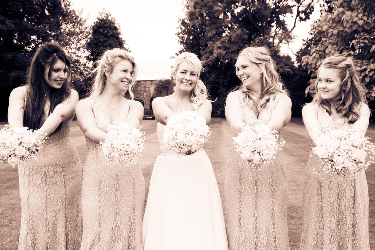Bride stood with her bridesmaids, posing with their bouquets in the Puckrup Hall gardens.