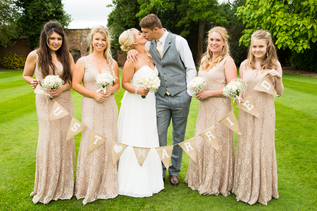 The bride and groom stood kissing, with the bridesmaids on either side holding up Just Married bunting.