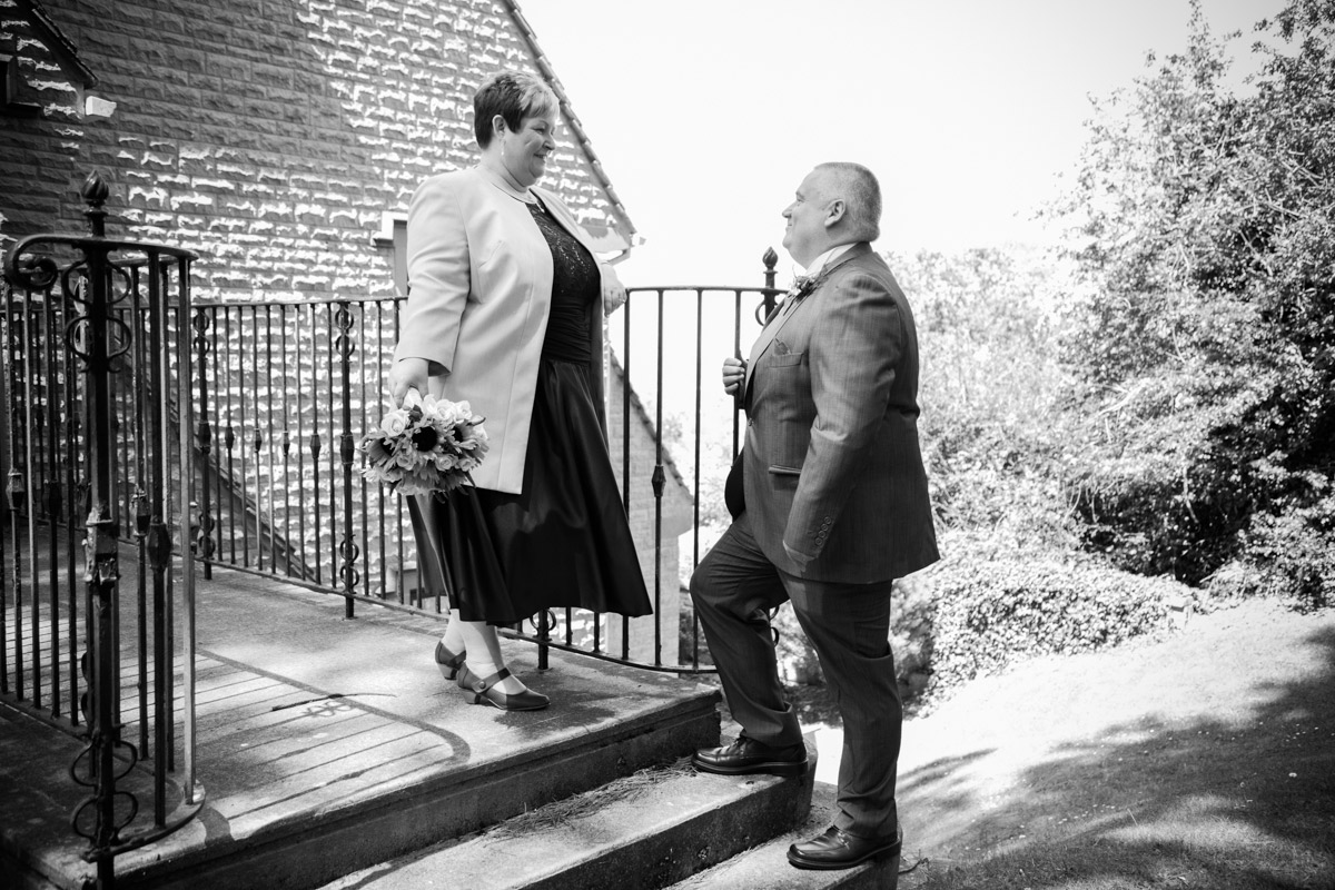 Groom looking up the steps at his bride at their hatton court hotel wedding