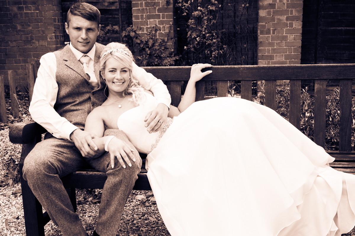 The bride and groom on a bench at Puckrup Hall.