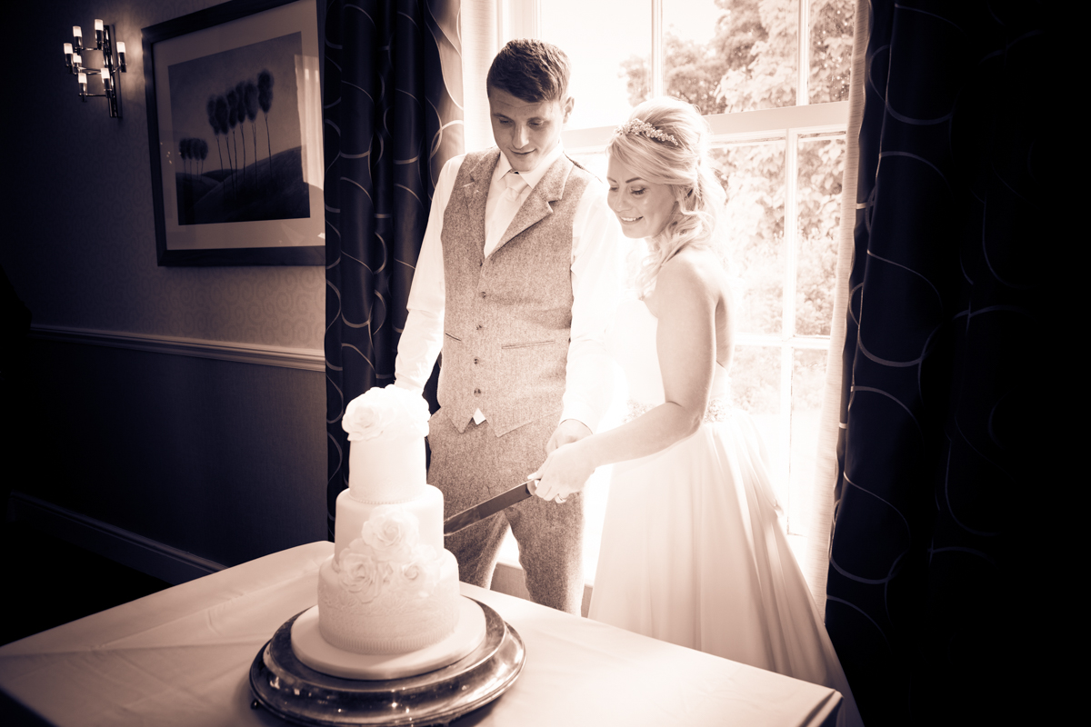 The bride and groom cutting their wedding cake at their Puckrup Hall wedding.