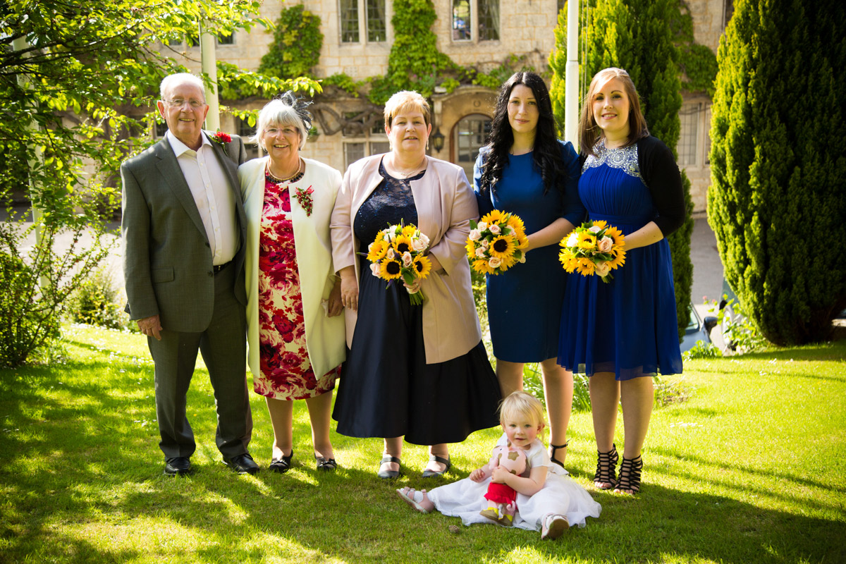 Bride stood on the grass with her parents, daughters and granddaughter.