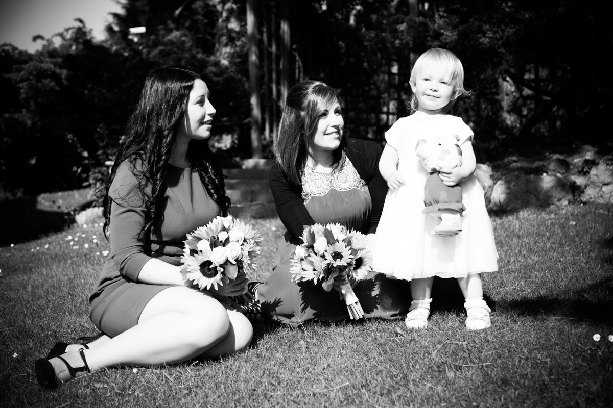 Bridesmaids sat on the grass looking at the young flower girl.